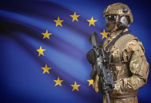Soldier in helmet holding machine gun with national flag on background - European Union